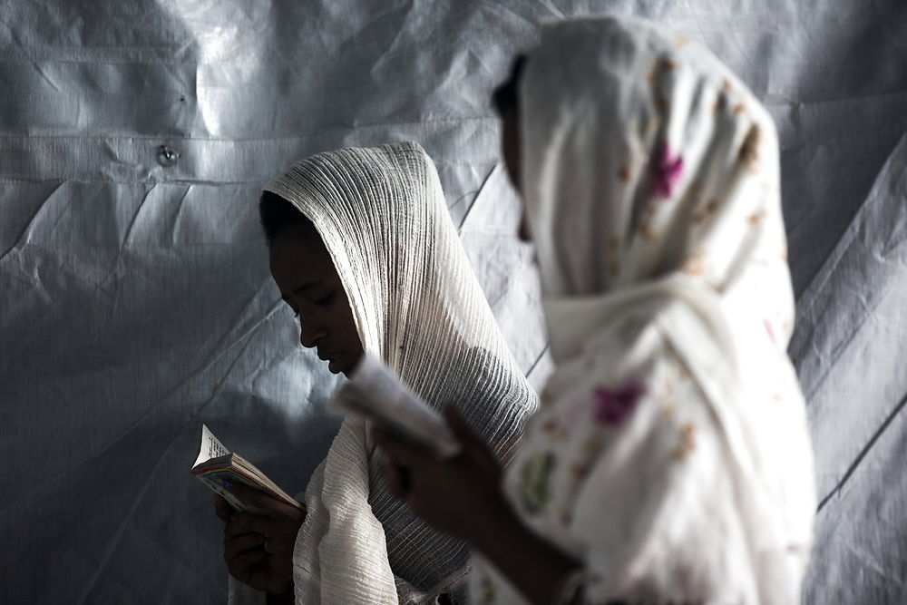epaselect epa04875963 Two migrant women from Eritrea pray in a small church they have built at the makeshift ...
