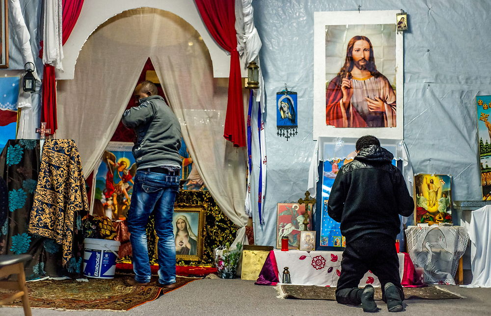 epa05080876 Refugees pray at the camp's church in the refugee camp during Christmas Day in the camp ...