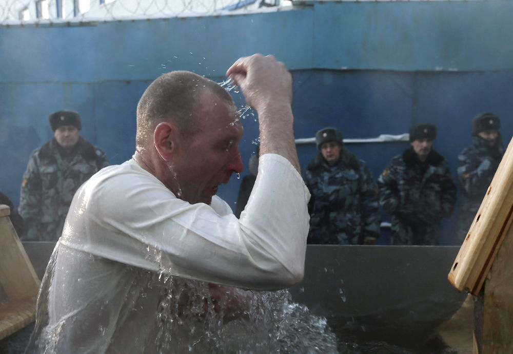 An inmate immerses himself in water at high-security penal colony number 6 on the eve of the Orthodox ...