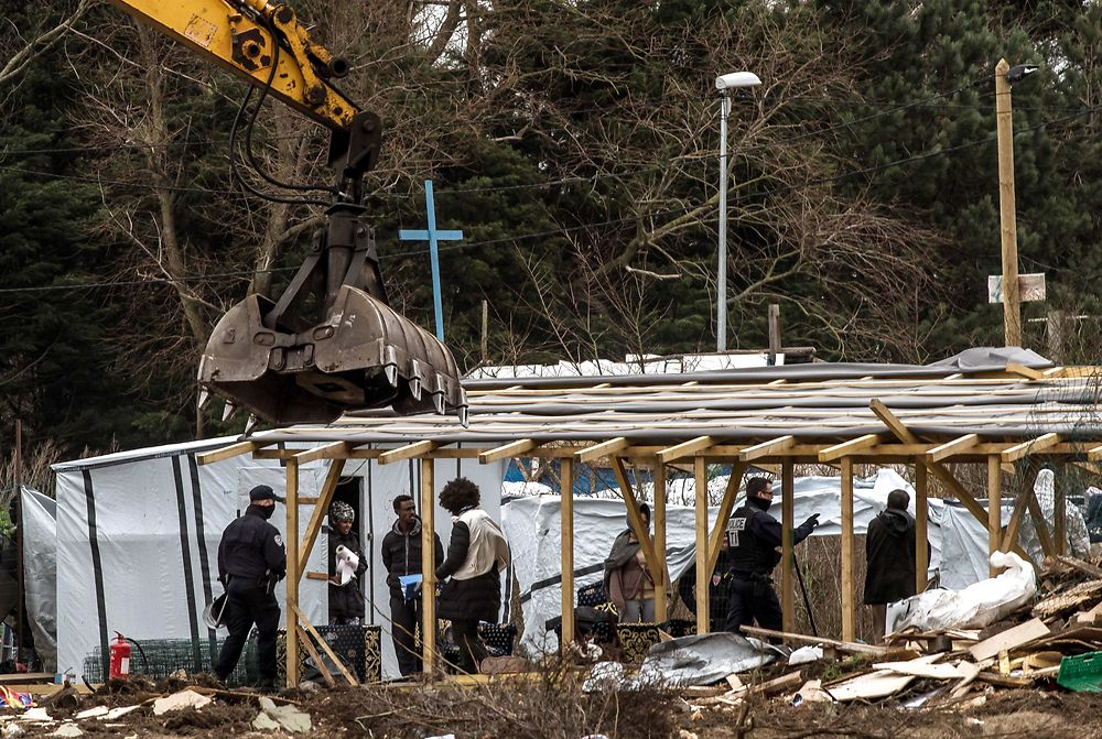 French police officers stand guard as an excavator knocks down buildings including a makeshift mosque and ...