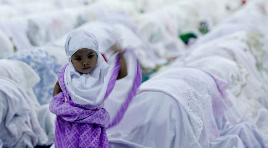 A child stands among Muslims attending prayers on the eve of the first day of the Islamic fasting month of ...