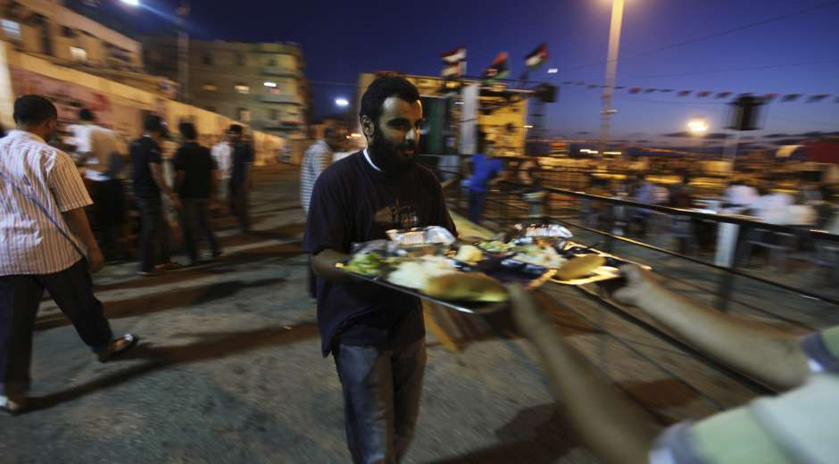 Muslim men prepare to break their fast at the end of the second day of Ramadan near the court house in ...