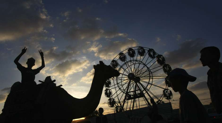 A Palestinian boy gestures from the back of a camel as he plays with friends at an amusement park in Gaza ...