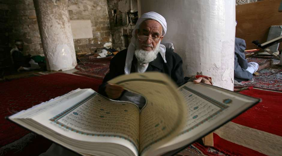 An elderly Yemeni man reads the Koran, Islam's holy book, at the Grand Mosque during the fasting month ...