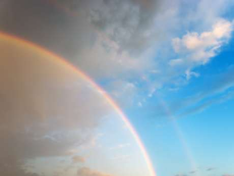 Optical phenomenon - effect of a double rainbow in beautiful cloudy sky