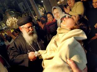 TO GO WITH STORY BY CHARLES ONIANS: Coptic priest Father Makari attends to a woman said to be ...