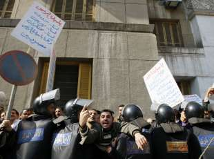 """Egyptian riot policemen stop protesters from approaching the parliament building in downtown Cairo during a demonstration on January 19, 2011 by traders and businessmen calling for improved economic conditions and trade laws in the country, as Arab League chief Amr Mussa warned Arab leaders at a Sharm el-Sheikh economic summit that the grievances of ordinary Tunisians which sparked a popular uprising were linked to """"unprecedented anger"""" in the region due to poverty, unemployment and general recession. Arabic writing on placard (L) reads: """"Mr. President, we are not riggers nor smugglers nor monopolists and we are all Egyptians."""" AFP PHOTO/MOHAMMED ABED"""