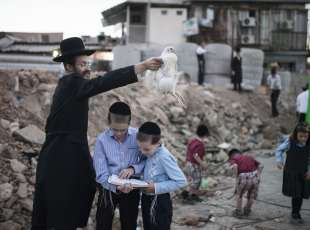 Ultra-Orthodox Jews perform the Kapparot ritual, where a person swings a live chicken or a bundle of coins ...