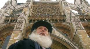 An actor dressed as Charles Darwin poses for photographs during a photocall at Westminster Abbey, in London ...