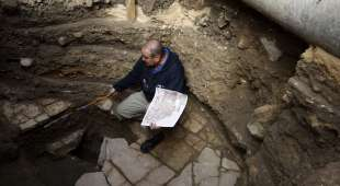 Excavation Director for the Israel Antiquities Authority Dr. Ofer Sion holds a replica of an ancient map as ...
