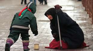 MOS01-19981231-MOSCOW, RUSSIAN FEDERATION: An old beggar woman sitting on a cold street in downtown Moscow ...