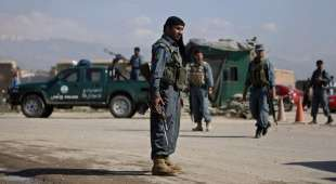 Afghan policemen keep watch at the checkpoint at the road leading to the U.S. airbase in Bagram May 19, 2010. ...