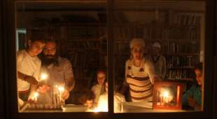 epa02477093 A Jewish family light candles on the second night of the Jewish holiday of Hanukkah in their ...