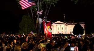 People react outside the White House after President Barack Obama announced that Osama bin Laden was killed, ...