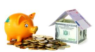 Piggy bank, gold coins and banknotes of the house is isolated on a white