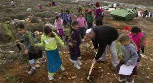 Jewish settler girls prepare to plant seedlings outside the West Bank settlement of Kiryat Arba, near Hebron, ...