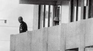 A Palestinian guerilla member (C) appears on the balcony of the Israeli house watching an official (L) 05 ...