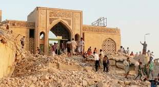 People walk through the rubble of the Prophet Younis Mosque after it was destroyed in a bomb attack by ...