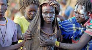 YEAREND REVIEW 2014: WOMEN'S ISSUES A Pokot girl, covered in animal skins, walks to a place where she ...