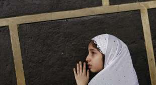 A Muslim girl touches the holy Kaaba at the Grand Mosque on the first day of Eid al-Adha during the annual ...