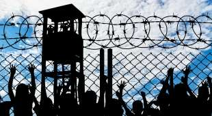 Silhouette of people viewing tower and refugees behind metal bars and barbed