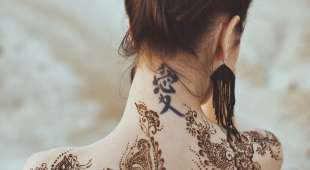Drawing mehndi by means of henna on hands and a back of the