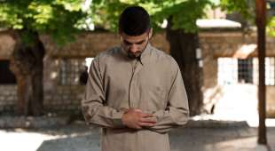 Young Muslim Man Making Traditional Prayer To God While Wearing A Traditional Cap