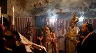 Syriac Orthodox priests pray during the Lent Sunday mass at the Church of the Holy Sepulchre while Catholics ...