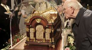 A man kisses the relics of Saint Therese of Lisieux in Westminster Abbey on October 12, 2009. Relics of a ...