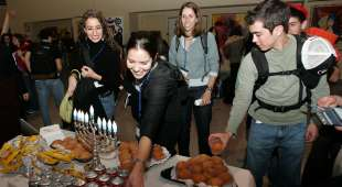 A group of youngsters enjoy a 'Sufgania' (Chanukah doughnut) at  JFK International Airport while ...