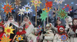 Ukrainians in folk costumes hold symbols of the star of Bethlehem as they celebrate Orthodox Christmas in ...