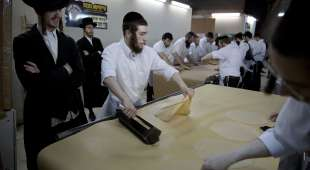 Jewish Orthodox men watch bakers make matza, a traditional handmade Passover unleavened bread, at a Tzanz ...