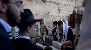 Covered in prayer shawls, ultra-Orthodox Jewish men read from a Thora scroll during the Jewish holiday of ...