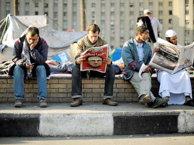 Anti-government protesters read the newspapers as they wake up inside Tahrir Square in Cairo February 12, ...