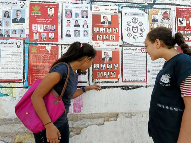 Tunisian girls look at election posters put up on a street ahead of the parliamentary election in the Tunis ...