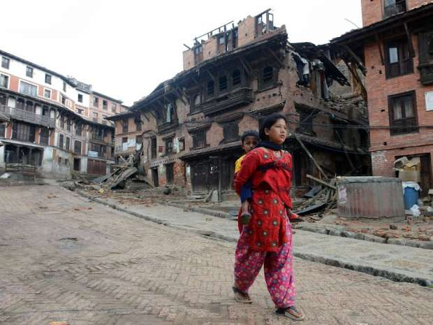 TOPSHOTS A woman carries a child next to collapsed houses in Bhaktapur, on the outskirts of Kathmandu, on ...