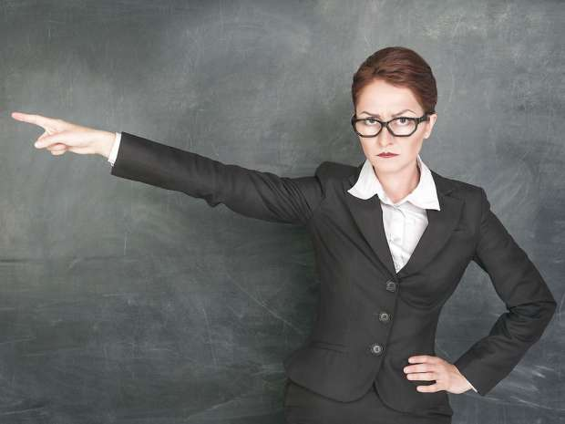 Angry teacher in glasses pointing