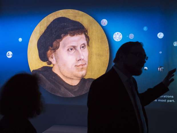 Visitors stand in front of a video installation displaying a portrait of Martin Luther during the press ...