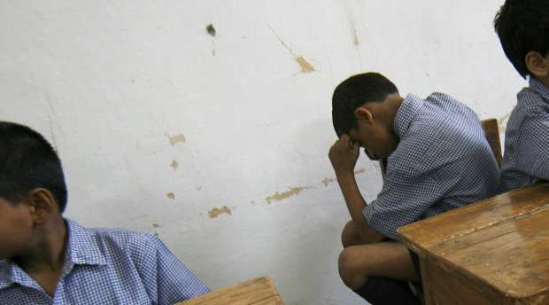 Students sit inside a classroom as they wait for their teacher at a school for the visually impaired in New ...