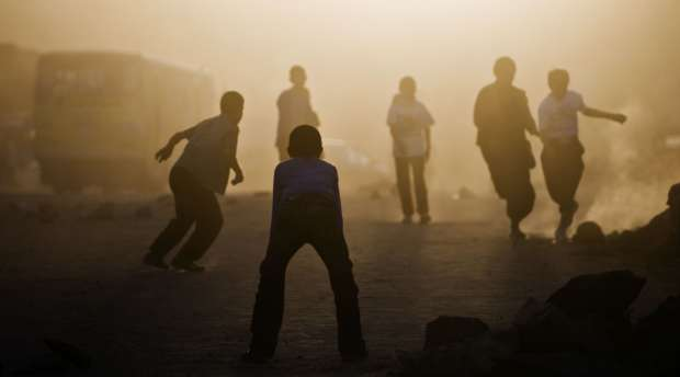 Afghan children play soccer at sunset in Kabul on August 19, 2009 on the eve of Presidential elections. ...