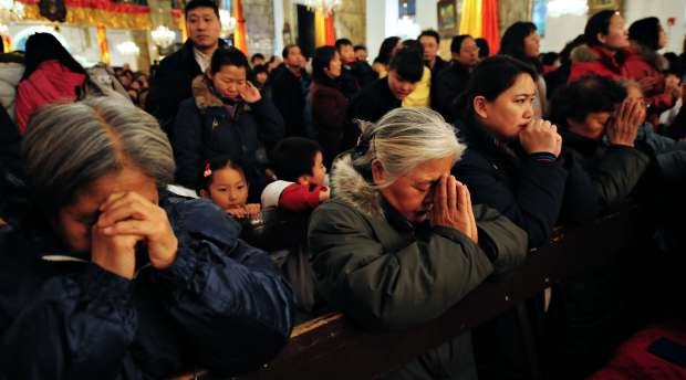 Chinese Catholics pray during a Christmas eve mass at The Cathedral of the Immaculate Conception, also known ...