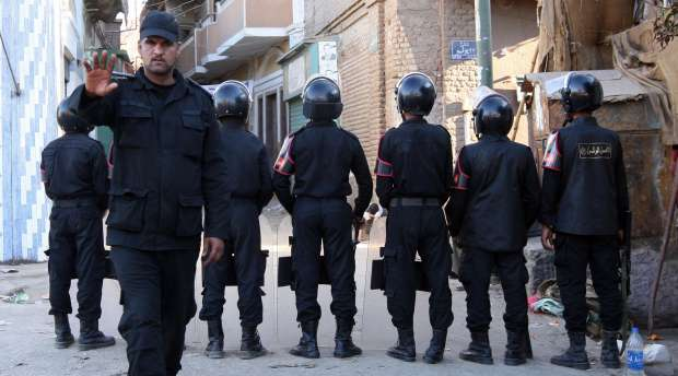 An Egyptian policeman gestures not to take photos as police stand guard in a street in the southern Egyptian ...