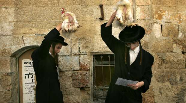 Ultra-Orthodox Jews swing chicken above their head during the Kaparot ceremony in Mea Shearim (one hundred ...