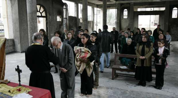 Saint George Catholic Church, destroyed by a bomb attack on October 16th. Father Vincent celebrates mass. ...