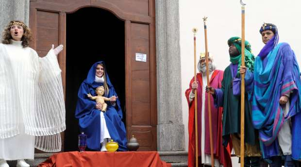 Men dressed as the three Wise Men (R) stand outside the church next to a woman dressed as mother Maria (C) ...