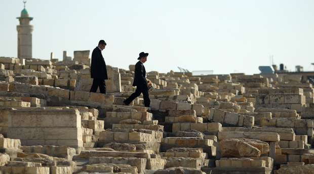 epa02545229 Two young Ultra-Orthodox Jewish men walk amid tombstones on the Mount of Olives in Jerusalem, on ...