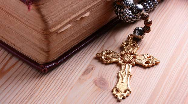Religion. A cross with a chain against a wooden