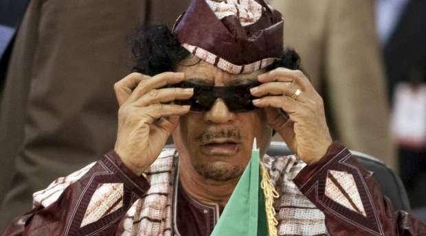 Libya's leader Muammar Gaddafi adjusts his glasses at the Africa-South America Summit on Margarita ...