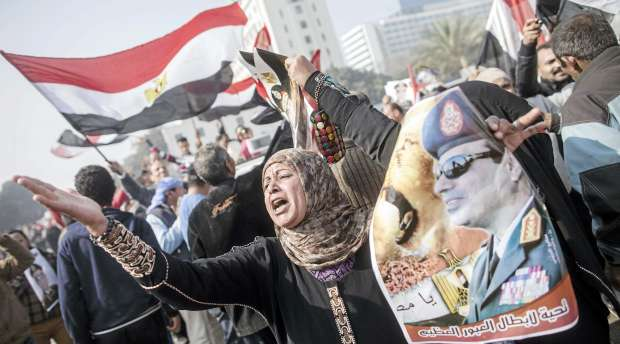 TOPSHOTS An Egyptian supporter of the military-installed government holds a poster bearing a portrait of ...