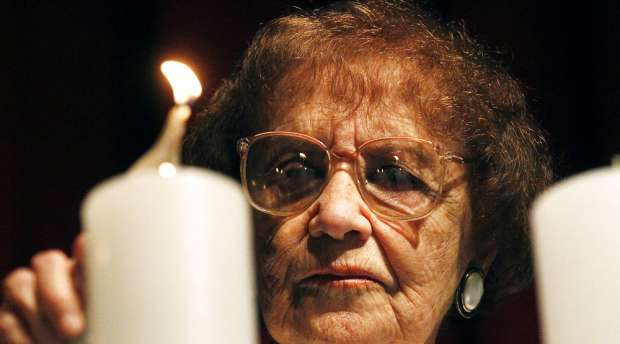 Auschwitz's survivor Lea Novera lights a candle while attending a ceremony during the International ...